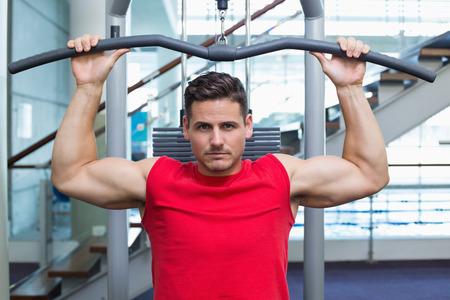 weight machine: Handsome bodybuilder using weight machine for arms at the gym