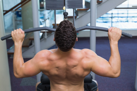 weight machine: Shirtless bodybuilder using weight machine for arms at the gym