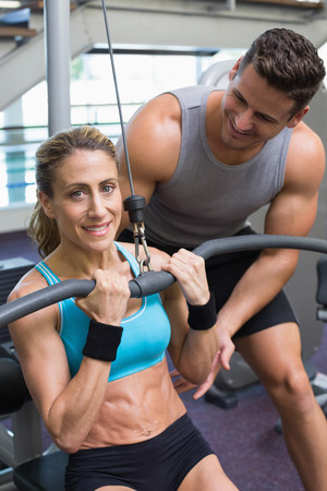 weight machine: Female bodybuilder using weight machine for arms with encouraging trainer at the gym