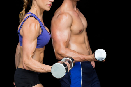 Bodybuilding couple posing with large dumbells on black background photo