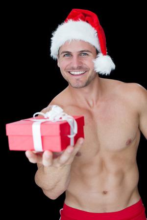 Homem muscular de sorriso que levanta no equipamento de Santa sexy oferta presente no fundo preto