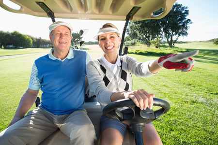 Happy golfing couple sitting in golf buggy on a sunny day at the golf course photo