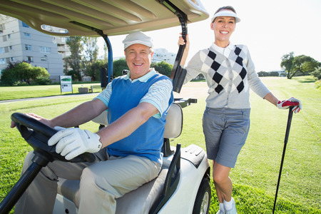 Happy golfing couple setting out for the day on buggy on a sunny day at the golf course photo
