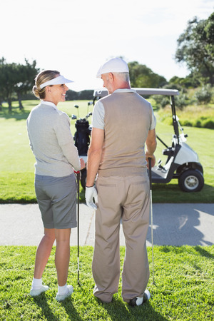 Happy golfing couple smiling at each other on a sunny day at the golf course photo