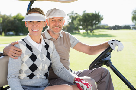 Happy golfing couple driving in their buggy smiling at camera on a sunny day at the golf course photo