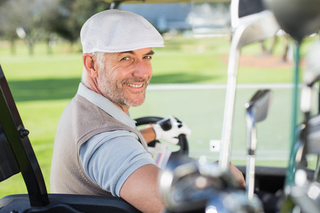 Happy golfer driving his golf buggy smiling at camera on a sunny day at the golf course photo