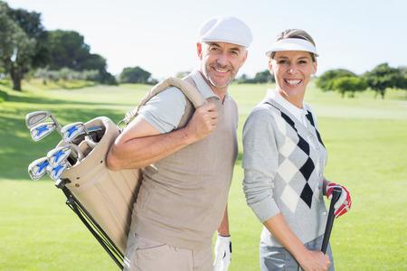Golf en pareja sonriendo a la cámara en el green en un día soleado en el campo de golf