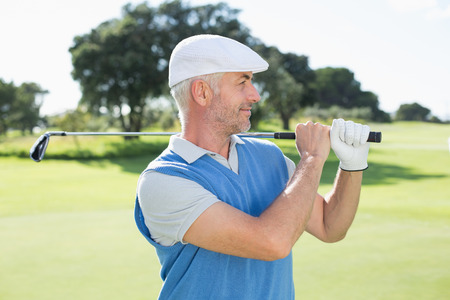 Golfer standing and swinging his club on a sunny day at the golf course photo