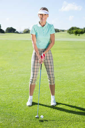 Lady golfer teeing off for the day smiling at camera on a sunny day at the golf course photo