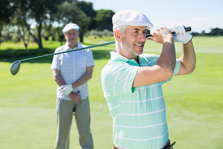 Golfer swinging his club with friend behind him on a sunny day at the golf course photo