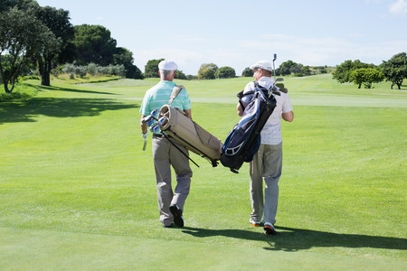 Golfer friends walking holding their golf bags on a sunny day at the golf course photo