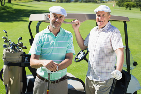 Golfing friends standing beside their buggy smiling at camera on a sunny day at the golf course photo