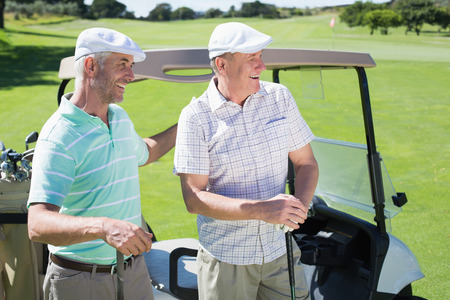 Golfing friends standing beside their buggy smiling on a sunny day at the golf course photo
