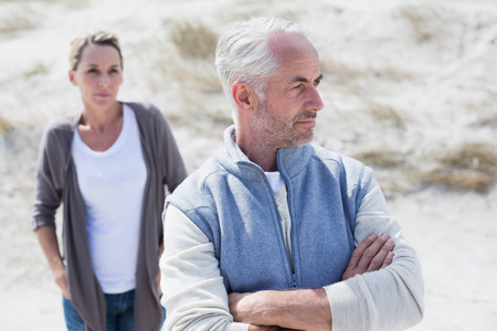 not talking: Couple not talking after argument on the beach on a bright but cool day Stock Photo