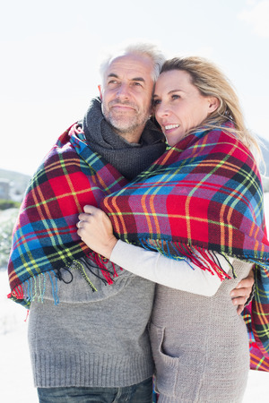 hair wrapped up: Happy couple wrapped up in blanket standing on the beach on a bright but cool day Stock Photo
