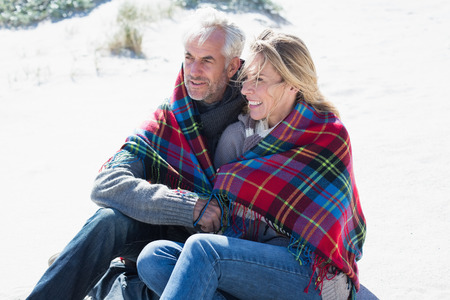 hair wrapped up: Happy couple wrapped up in blanket sitting on the beach on a bright but cool day