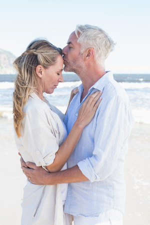 Man kissing his partner on the forehead at the beach on a sunny day photo