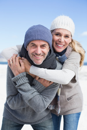 Attractive couple hugging and smiling at camera on the beach in warm clothing on a bright but cool day photo