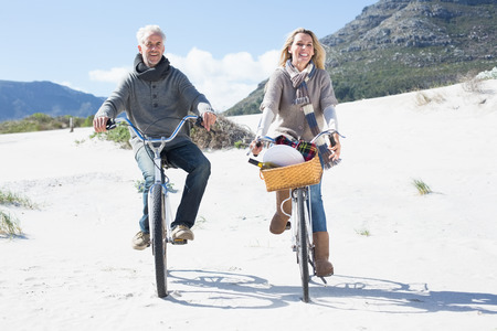 Carefree couple going for a bike ride and picnic on the beach on a bright but cool day