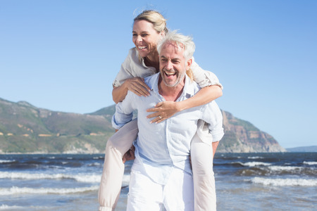 50s man: Man giving his laughing wife a piggy back at the beach on a sunny day Stock Photo