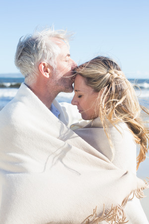 wrapped up: Affectionate couple wrapped up in blanket on the beach on a sunny day Stock Photo