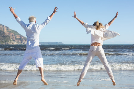 Couple jumping on the beach together on a sunny day photo