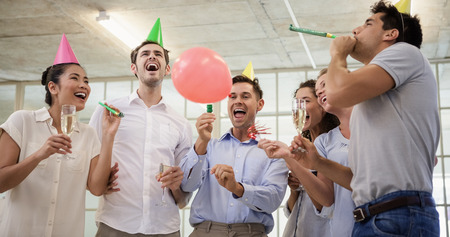 party popper: Casual business team celebrating with champagne and party horns in the office Stock Photo