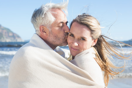 hair wrapped up: Smiling couple wrapped up in blanket on the beach on a sunny day