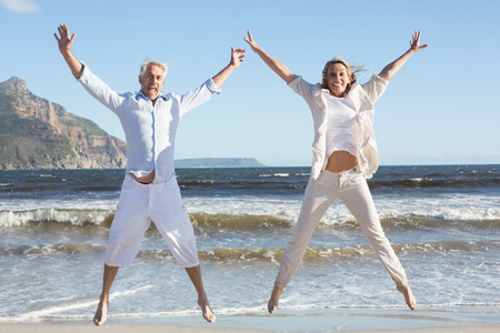 escapism: Happy couple jumping on the beach together on a sunny day