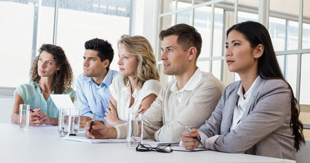 Casual business team listening during meeting in the office photo