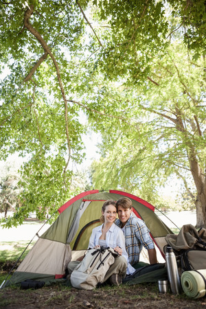 adventuring: Happy couple sitting in their tent after a hike and looking at camera on a sunny day