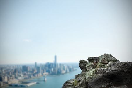 coastline: Digitally generated large rock overlooking coastline city
