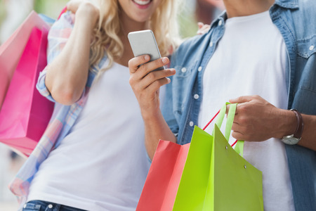 Cute young couple on shopping trip looking at smartphone  on a sunny day in the city photo