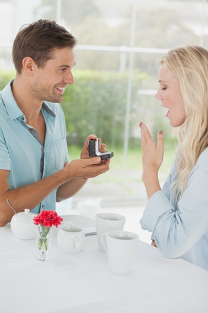 Man surprising his girlfriend with a proposal in cafe on a sunny day in the city photo