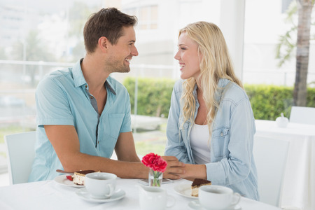 Hip young couple having desert and coffee together on the cafe terrace on sunny day photo