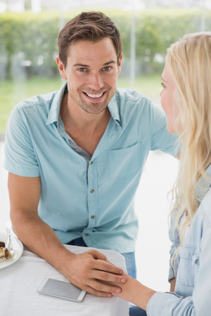 Hip young couple sitting at table on the cafe terrace on sunny day photo