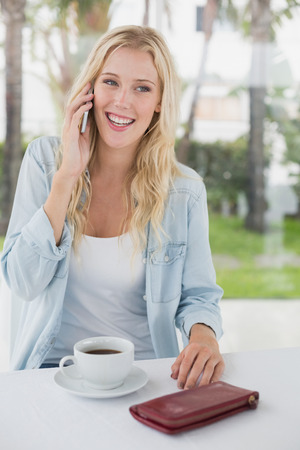 Pretty blonde sitting at table having coffee talking on phone on the cafe terrace on sunny day photo