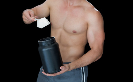 scooping: Muscular man scooping up protein powder on black background