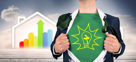 Businessman opening shirt in superhero style against diagram of a house with energy rating chart  Stock Photo