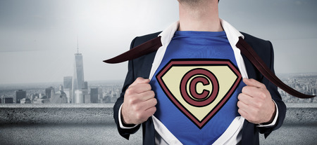 copyright: Businessman opening shirt in superhero style against balcony overlooking city Stock Photo