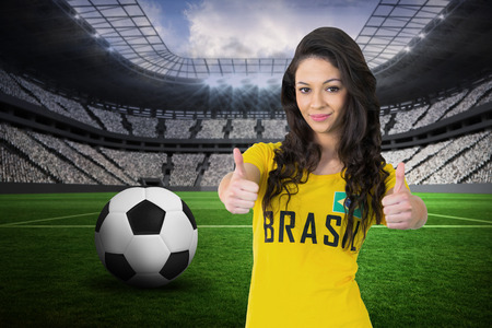 Pretty football fan in brasil tshirt against vast football stadium with fans in white photo