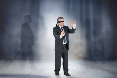 Composite image of mature businessman in a blindfold against grey room