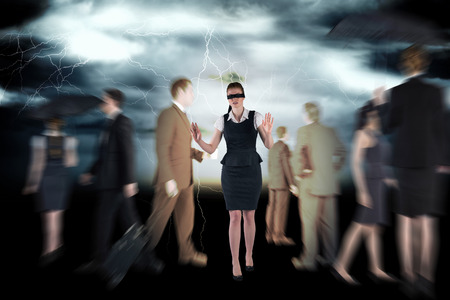 Redhead businesswoman in a blindfold against stormy dark sky with lightning bolts photo