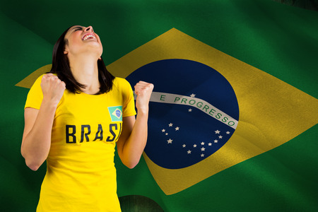 Excited football fan in brasil tshirt against digitally generated brazil national flag photo