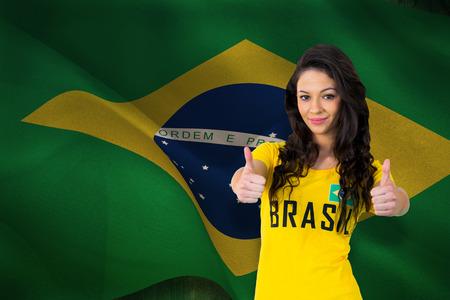Pretty football fan in brasil tshirt against digitally generated brazil national flag photo