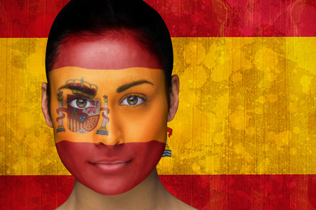 Composite image of beautiful football fan in face paint against spain flag in grunge effect photo