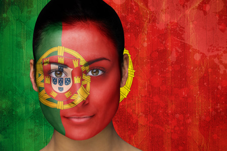 Composite image of beautiful football fan in face paint against portugal flag in grunge effect photo