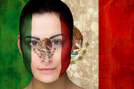 Composite image of beautiful football fan in face paint against mexico flag in grunge effect photo
