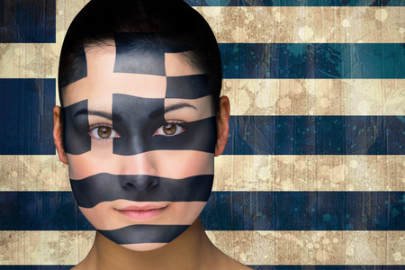 Composite image of beautiful football fan in face paint against greece flag in grunge effect photo