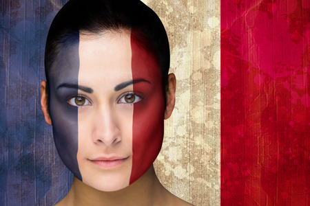 Composite image of beautiful football fan in face paint against france flag in grunge effect photo